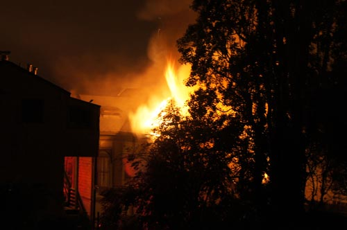 We live on the block behind the house that caught fire early this morning on the 2900 block of Lorina Street between Russell Street and Ashby Avenue. It was pretty intense, and from our roof the situation didn't look good because the fire engulfed the back side of the house, making it difficult for the fire fighters to get to it. I could see our neighbors in their back yards, and fire fighters going through the back yard directly behind the fire for a better look. Everyone living on this side were concerned that the huge tree in the fore-ground of these photos would burn as well. We could see smoke billowing out from the front of the house too, so we were concerned that it might get out of control.