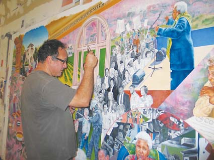 Daniel Galvez puts the final touches on the mural he created with Mildred Howard celebrating the life of 20-year former Berkeley City Councilmember Maudelle Shirek. Photograph by Judith Scherr.