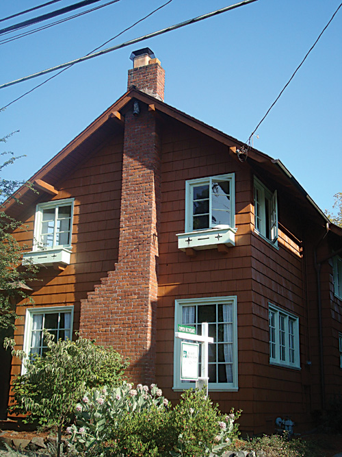 The shingled 2512 Russell St. has chimney, window boxes, and casement windows on the street façade.
