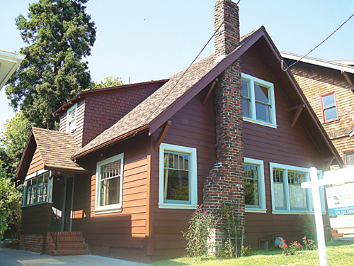 584 61st St. has horizontal board siding, double-hung windows, and a clinker-brick chimney.