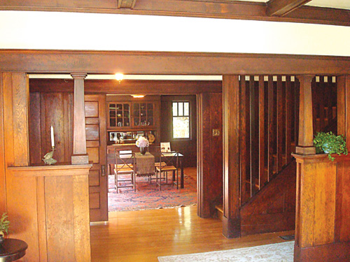 The view from living room to hall to dining room at the Oakland house is lavishly filled with original redwood details.