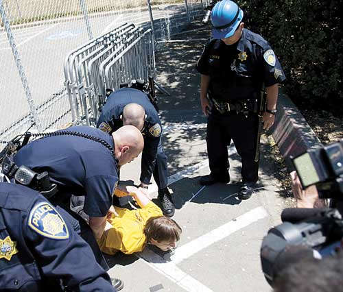Tree-sit supporter Matthew Taylor struggles with campus police after he was wrestled to the ground and arrested during Sunday's protest outside Memorial Stadium.