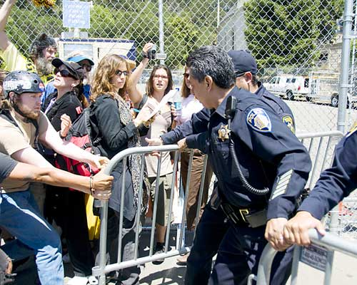 UC Berkeley Assistant Police Chief Mitch Celaya struggles to close the breach between two barriers opened by tree-sit supporters who wanted to resupply the nine remaining protesters at the Memorial Stadium grove slated for destruction to make way for a new gym complex.