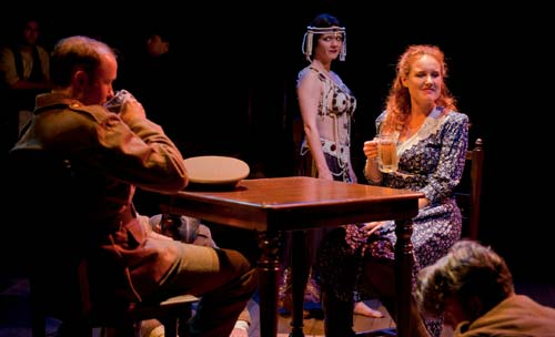 A soldier on leave (l. Alex Moggridge*) has a pint with a local (r. Marilee Talkington*) and chats about Maud Allan's circus of a libel trial as Maud (c. Madeline H.D. Brown*) and pub regulars (back l-r, Liam Vincent* and Anthony Nemirovsky*) look on in the World Premiere