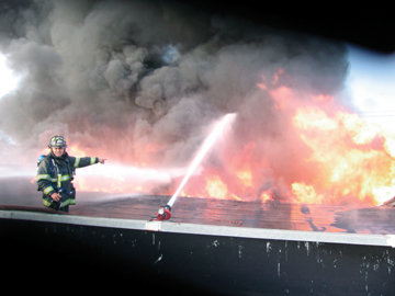 Dave Sprague, Berkeley Firefighter: A Berkeley firefighter battles the flames from a roof adjoining the Berkeley Rep's set workshop at Fifth and Gilman streets Wednesday night.