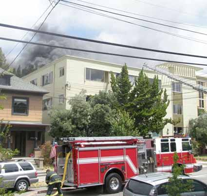 Dense black smoke pours from two third-floor residences in the Rus-Tel Apartments during a two-alarm blaze that began shortly before noon Tuesday.
