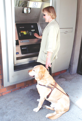 LAURA OFTEDAHL and her dog Victor use a Bank of America ATM in Berkeley that is formatted for the visually-impaired.