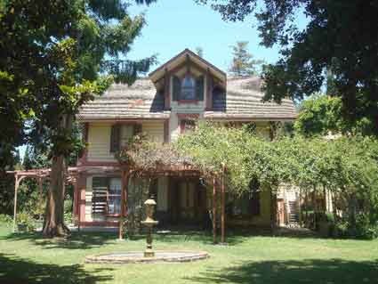 The wooden Victorian style Shinn House dates to the 1850s and showcases four generations of Shinn family artifacts and early Alameda County rural life. Beyond the rose arbor on the right a two-story water tower rises.