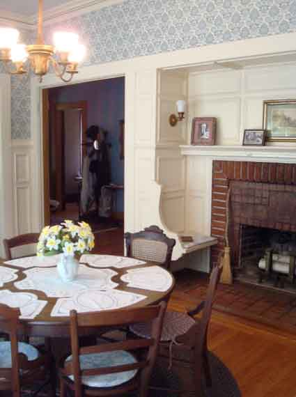"The ""day room"" has a round dining table where the adult members of the family often ate, a fireplace with inglenook seating, and a safe (empty) concealed behind one of the wooden panels."