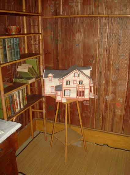 A needlepoint model of the house made by a volunteer sits in the corner of a bedroom that features painted bamboo wall coverings.
