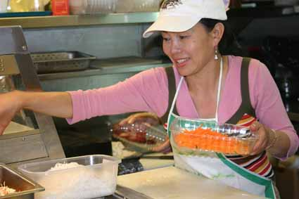 Healthy Heavenly Foods proprietor Ann Vu prepares Vietnamese chicken noodle salad at her shop at the Bear's Lair Food Court Monday morning.