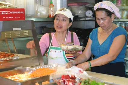 Ann Vu and Dona Ngo, a Healthy Heavenly Foods employee for 12 years, serves lunch to UC Berkeley students and staff Monday.
