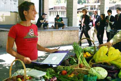 UC Berkeley alumna Alex Stone sets up the produce stand on Upper Sproul Hall Monday to inform students about the Berkeley Student Food Cooperative.