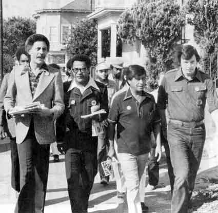 Tom Bates strolling down the streets of Oakland with John George, Ron Dellums, and Cesar Chavez  as they campaign door to door.