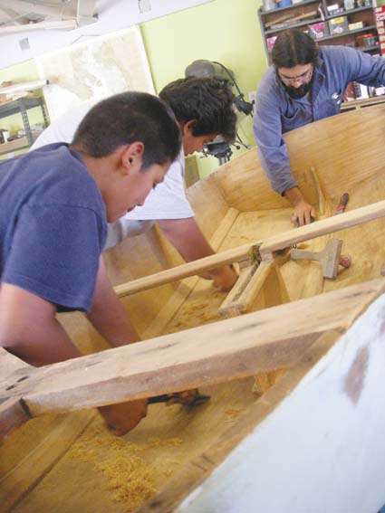 Helder Parreira shows brothers Miguel and Alvaro Hernandez how to build a boat at the Aquatic Park's revamped Berkeley Boathouse last week. Photograph by Riya Bhattacharjee.