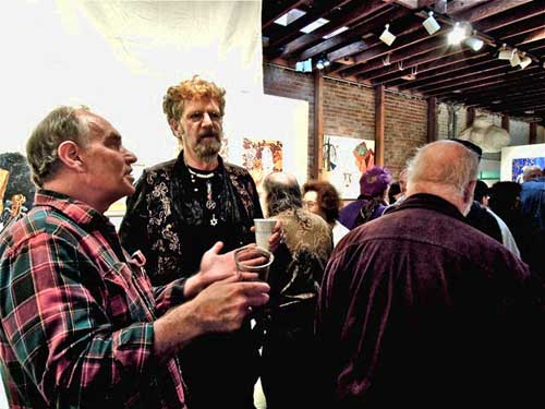 Opening night, Saturday, for Debbie Vinograd's and Tom Tuthill's art show at AutoBody Art-Space, Alameda. San Francisco artist, Chris Trian, is center (in colorful vest).