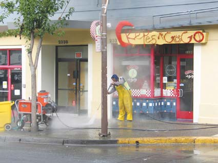 A worker power washes the sidewalk Tuesday morning on Telegraph Avenue. Sprucing up the sidewalks is part of a plan to bring business back to The Avenue. Photograph by Judith Scherr.
