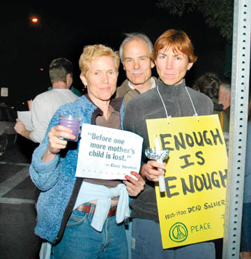 Richard Brenneman: Tina Estes, Left, Jamie Elmer, and Val Hammell greeted passing motorists with signs and candles along with hundreds of others who gathered outside the French Hotel Wednesday night in a vigil to support anti-war activist Cindy Sheehan's ongoing vigil outside the Crawford, Texas, ranch of President George W. Bush..
