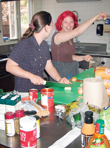 Matthew Artz: Graduate students Lauren MacKinnon, with knife, and Samara Vachss, both residents of the new Hillegass-Parker House, prepare dinner Tuesday for the first house meeting.