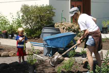 LeConte parent Carly Strouse and her son Marlow Buettner—wearing a Superman cape—rake mulch in the school's new garden Friday.