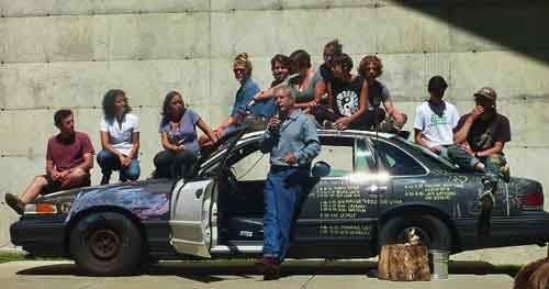 "Farmer Paul Cannard spoke from in front of a student festooned ""police car""
