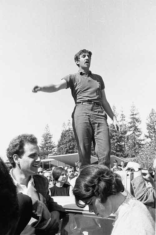 Jack Weinberg speaking from top of police car. Mario Savio standing on ground in foreground.