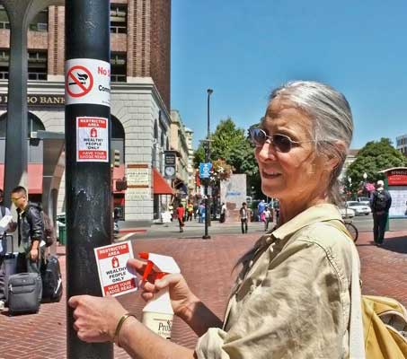 "Poster girl. Carol Denney, Berkeley activist, who has postered Berkeley since 1972, posters Sunday in Constitution Square (at downtown Bart entrance). Above her restricted area poster (""Wealthy People Only) is a ""No Smoking"" sign.  The glop running down the pole is her own special-formula glue, shot from her spray bottle."