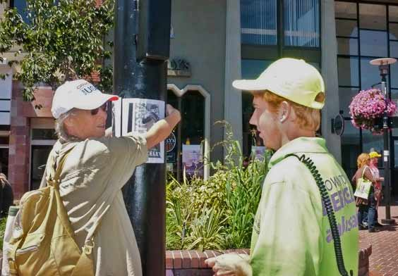 "Denney protecting her poster from a downtown host-ambassador. Poster says: ""Fascism...it starts here...Downtown Berkeley."