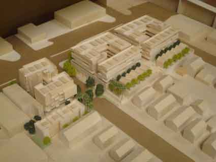 "The model photograph shows the buildings stepping down to the west, with a row of ""micro-cottages"" at the rear."