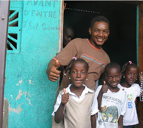 Herode Garry Laurent poses with three children he works with in Cité Soleil in front of a home converted to a clubhouse, affiliated with Pax Christi, to keep children from the impoverished shantytown off the street and to help break up the factionalism among youth that divides those from upper and lower Cité Soleil.