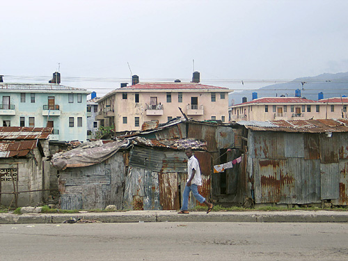 A Haitian man walks by shacks in a Port-au-Prince shantytown. Behind the shacks is a housing project, begun by former President Jean Bertrand Aristide, exiled from Haiti by the international community.