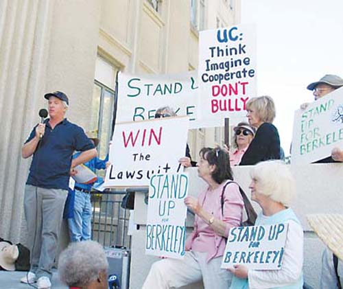 Doug Buckwald, organizer of the Stand Up Berkeley press conference and rally, addresses some 60 supporters and the press Tuesday afternoon, calling on the City Council to reject the university's offer to settle the city lawsuit on the proposed athletic training facility. Photograph by Judith Scherr.