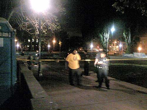 Police handcuff a man at Civic Center park following Wednesday night's shooting incident.