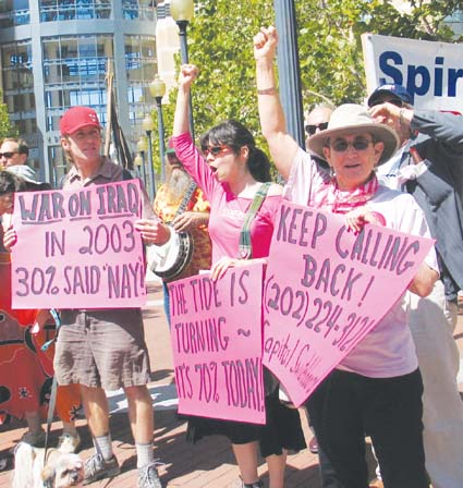 Demonstrators call on Congress to end funding for the war in Iraq at a demonstration called by Code Pink at the Oakland Federal Building on Tuesday. Photograph by Judith Scherr.