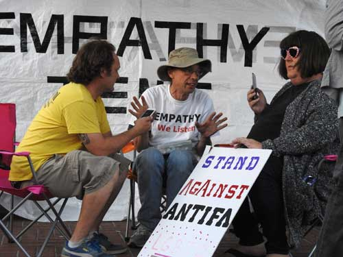 Amber Cummings, the self-designated (but no-show at least in this female persona) organizer of the August 27 right-wing non-rally at Berkeley's MLK Park, engages in dialogue with (presumably) a protester against Ben Shapiro's appearance on the UC Berkeley campus.  The Empathy tent,a fixture at recent contentious demonstrations, is maintained by volunteers who offer to listen to everyone.