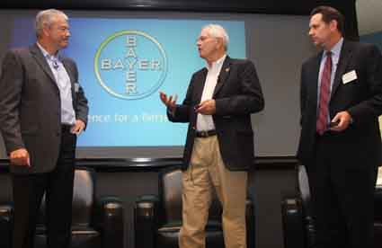 Berkeley Mayor Tom Bates talks to Bayer's Joerg Heidrich as Douglas Hoffner looks on during the announcement Wednesday that Bayer was staying in Berkeley.