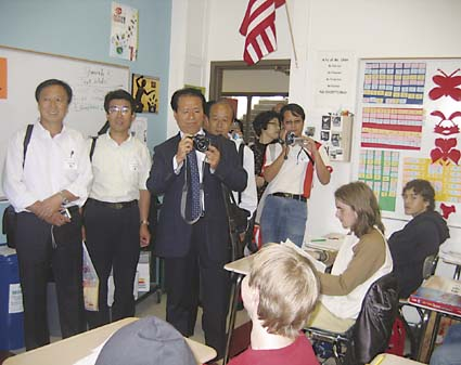 Members of the Chinese delegation of 17 principals from China's TangGu district of TianJin province take pictures and talk to students in Berkeley High School's Chinese Mandarin class Wednesday. Photograph by Riya Bhattachajee.