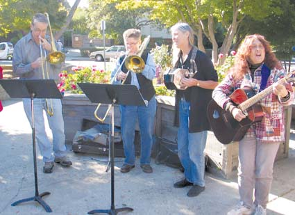"Making their political point musically outside Saturday's meeting on the Public Commons for Everyone Initiative (left to right), Jeffrey Carter, Pat Mullen, Carol Denney and Hali Hammer croon, ""Brother, Can You Spare a Dime."" Photograph by Judith Scherr."