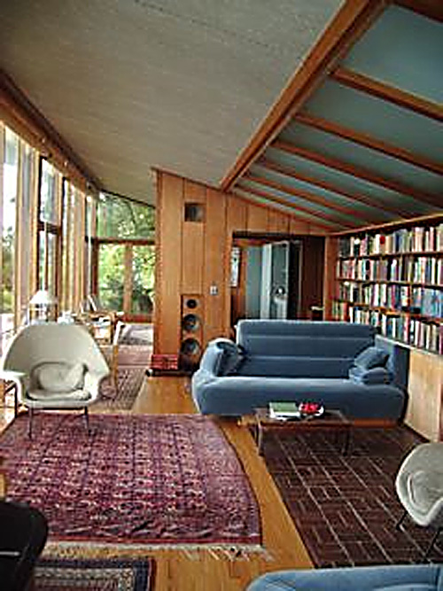 The Havens House living room has ceilings that slant up and outwards to expand the Bay view, and original furnishings collected by Weston Havens.