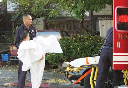 A Berkeley Fire Department paramedic carries the mother of 9-year-old Amir Hassan to a waiting ambulance after police discovered the injured woman and her dead son in the rear unit of a small apartment at 3011 Shattuck Ave. Wednesday morning.