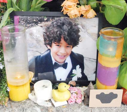 A photo of Amir Hassan is part of a memorial in front of the Shattuck Avenue house where he died. Photograph by Richard Brenneman.
