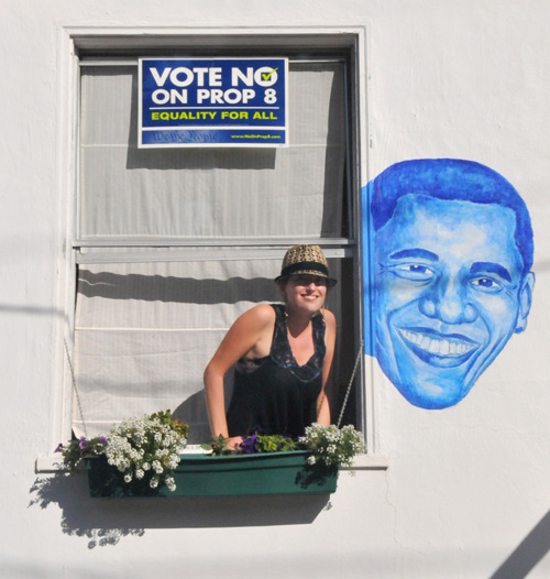 Artist Diana Hartman with her mural of Barack Obama on a McGee Avenue house on Wednesday.