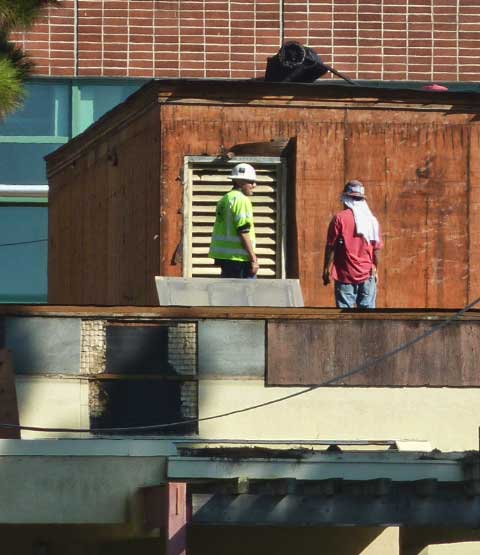 Construction workers on the roof of the old cafeteria this week. BUSD representatives at the meeting said there is no construction going on at that building. The building in the rear is under construction for separate use.
