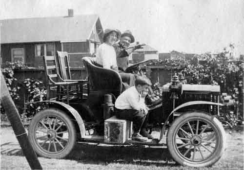A young Berkeley family takes off for an outing. Dining room chairs and a fruit basket provide some of the vehicle's seating.