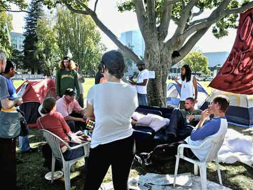 "Occupy Berkeley's encampment meeting Saturday in Civic Center Park before a ""grade-in"" to support the anti-Wall Street movement. Man seated at end of couch, to right, was hailed a hero for saving Friday's overnight tent occupation from a marauder"
