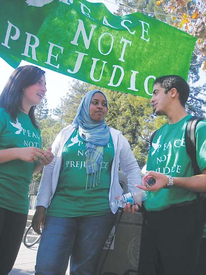 Hamzah Hararah, UC Berkeley Muslim Students' Association political action committee co-chair,  talks with Narmin Nuree (center), senior and a member of the Coalition for Peace Not Prejudice, on Sproul Plaza Wednesday. The coalition responded to Berkeley College Republican Islamo-Fascist Week with Peace Not Prejudice week. Photograph by Riya Bhattacharjee.