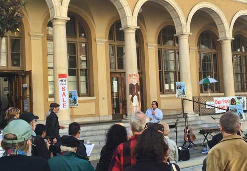 Councilmember Jesse Arreguin addresses the Save the Berkeley Post Office rally on Saturday morning.  Notables in the crowd: far left, District 8 Council candidate Jacquelyn McCormick; center in red checked shirt, Councilmember Linda Maio's husband, Rob Browning.