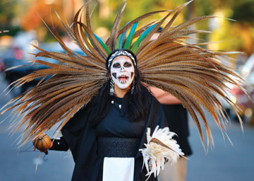 Jakob Schiller: Cristina Mariscal of the Cuauhtonal Aztec Dance group performs during a late-afternoon ceremony outside St. Elizabeth's Church as part of the Day of the Dead celebration in Oakland's Fruivale neighborhood on Sunday. The annual celebration mixes Indigenous Indian practices dating back to the Aztecs with more recent Mexican traditions, and is meant to remember and honor the dead.