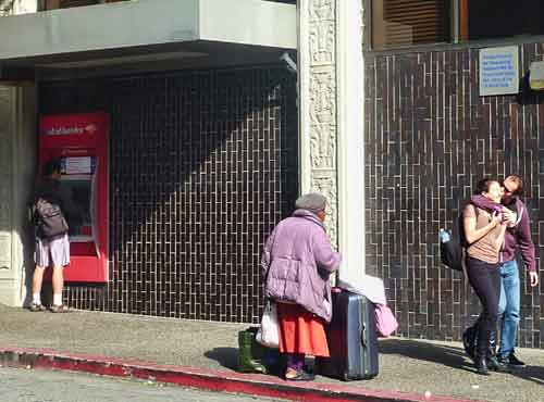 A solitary homeless woman panhandled in front of the Telegraph Avenue branch of the Bank of America in the quiet minutes before the march began.