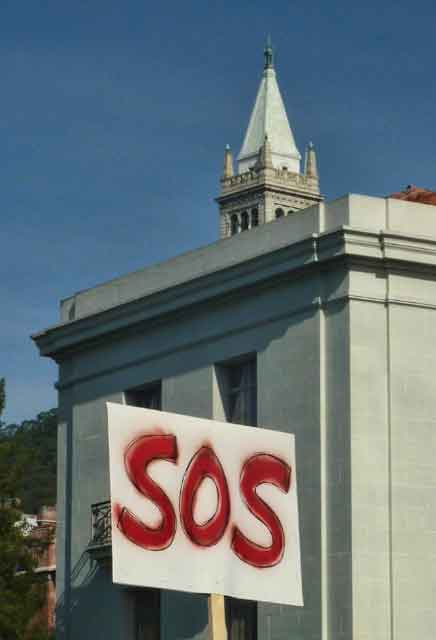 "A simple ""SOS"" appeal against the backdrop of Sproul Hall and the Sather Campanile."